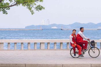 Cycling past, Wonsan, North Korea