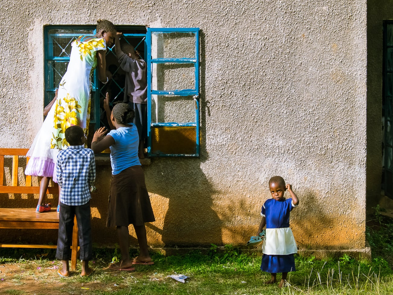 Children peeking in through a window at a church wedding in Kima, Kenya