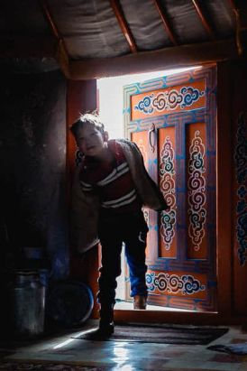 Boy entering Mongolian ger or yurt
