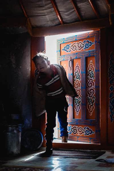 Boy entering Mongolian ger (yurt)