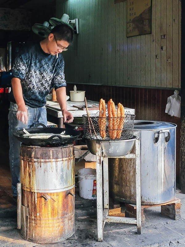 Man frying youtiao. Xitang ancient water town, Zhejiang, China