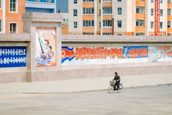 Man cycling past sign in Rason, North Korea