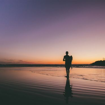 Man on beach at dusk. Photo: Jacob Repko / Unsplash