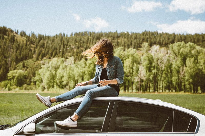 Woman on car with windblown hair. Photo: Averie Woodard / Unsplash