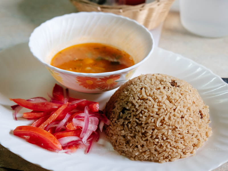 A plate of Swahili pilau with tomato and onion garnish